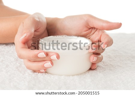 Woman holding cream isolated on white background - stock photo