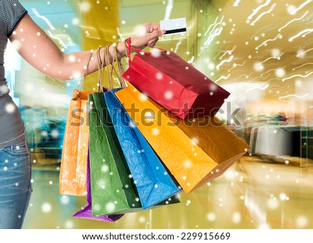 Woman holding credit card and shopping bags at shopping mall.  Christmas and holidays concept
