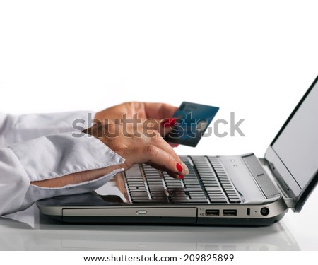 Woman holding credit card and writing on keyboard