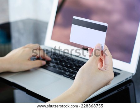 woman holding credit card in hand and entering information into a laptop, Shopping Online