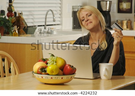 Woman holding credit card  in her kitchen Using her Laptop for Ecommerce. - stock photo