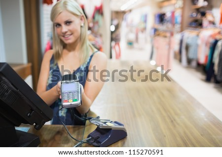 Woman holding credit card mahine in clothing store - stock photo