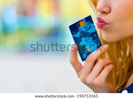 woman holding credit card near to her lips - stock photo