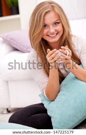 Woman holding cup of coffee and enjoying the smell of its aroma - stock photo