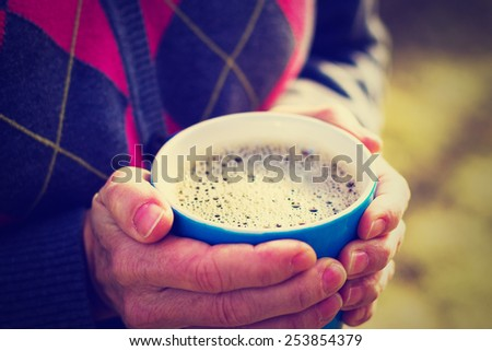 woman holding cup of coffee in the morning sun with a close-up of the cup with an instagram filter (shallow depth of field) - stock photo
