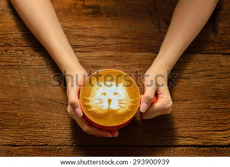Woman holding cup of coffee latte on wooden table - stock photo