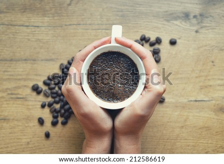 Woman holding cup of freshly brewed coffee. - stock photo