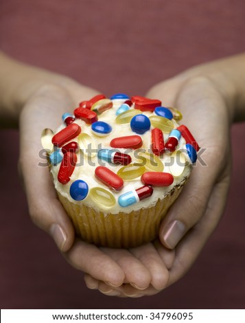 Woman holding cupcake decorated with pills, close-up of hands
