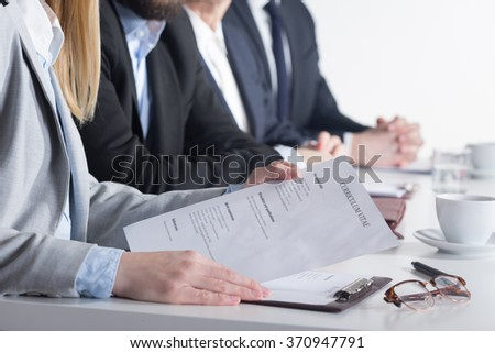 Woman holding CV sitting next to three businesspeople beside table