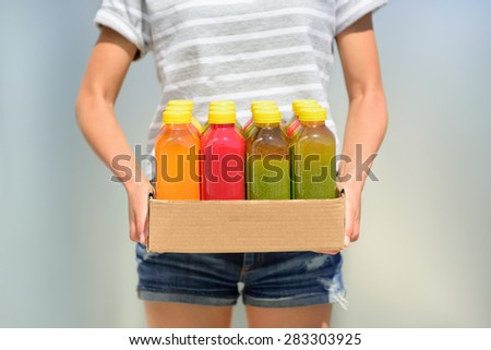Woman holding delivery box of freshly cold pressed fruit and vegetable juice bottles. Closeup of female person carrying organic raw juices. Juicing is a food trend for diet cleanse detox. - stock photo