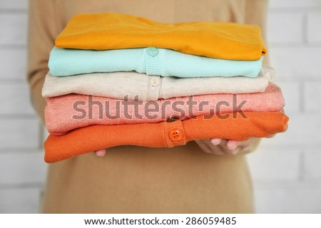 Woman holding different clothes, on bricks wall background - stock photo