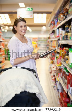 Woman holding digital tablet with baby stroller in foreground while looking at camera in shopping centre