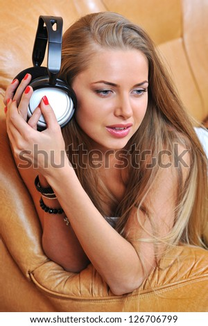 Woman holding earphones and listening to the music