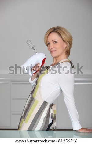 Woman holding electric whisk - stock photo