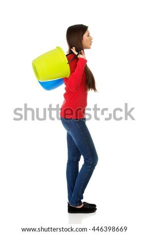 Woman holding empty plastic buckets. - stock photo