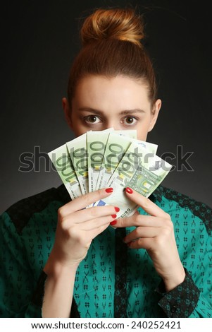 Woman holding euro banknotes, Close up of young woman covering her face with bunch of euro banknotes - stock photo