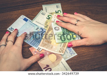 woman holding euro banknotes over wooden table. tinted photo