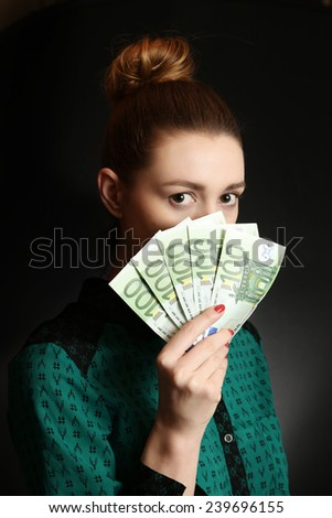 Woman holding euro bills, Close up of young woman covering her face with bunch of euro bills - stock photo