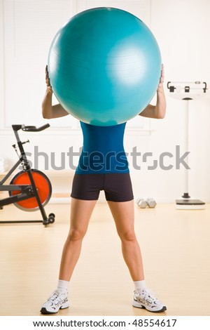 Woman holding exercise ball in health club - stock photo