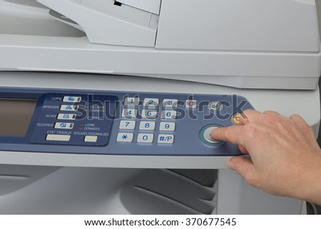 Woman holding finger on start button of laser printer