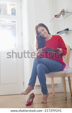 Woman holding footwear in store - stock photo