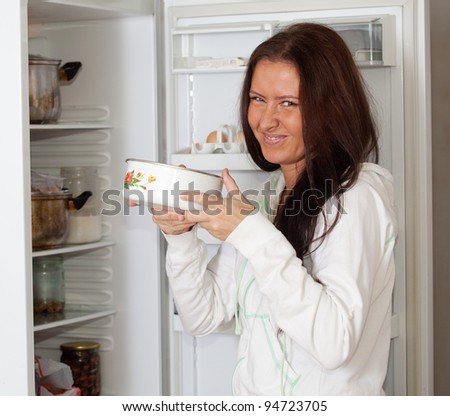woman  holding foul food  near refrigerator  at home - stock photo