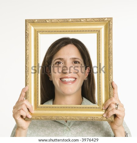 Woman holding frame in front of face smiling.