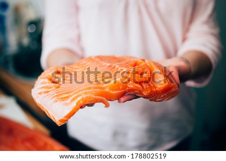 """Woman holding fresh piece of fresh raw salmon. Tilt-shift lens used to outline the food """" and to emphasize the attention on it  - stock photo"""