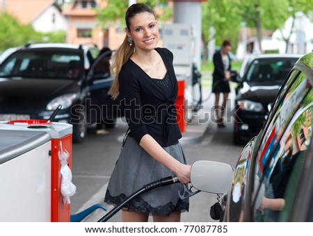 woman holding fuel nozzle and refuel car in gas station - stock photo