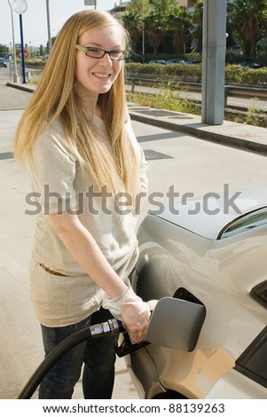 Woman holding fuel nozzle and refuel car in gas station. - stock photo