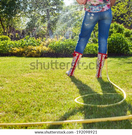 Woman holding garden water hose wearing colorful wellies watering garden  - stock photo
