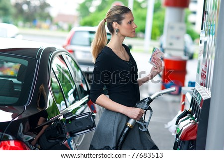 woman holding gas nozzle and money in gas station - stock photo