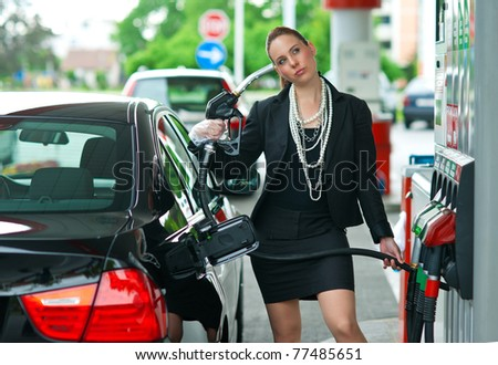 woman holding gas nozzle as gun pointed to her head - stock photo
