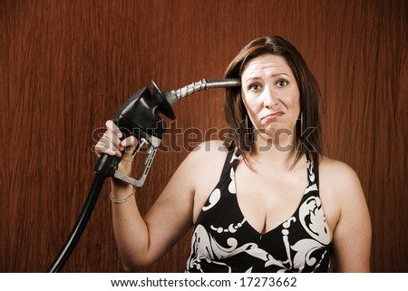 Woman holding gas nozzle like a gun to her head - stock photo