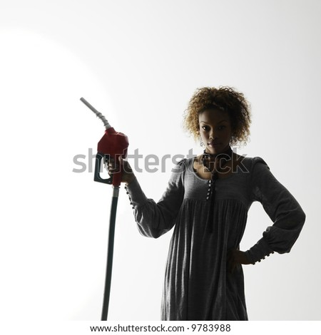 Woman holding gasoline pump nozzle against white background with dramatic studio lighting. - stock photo