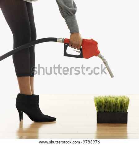 Woman holding gasoline pump nozzle over green grass. - stock photo