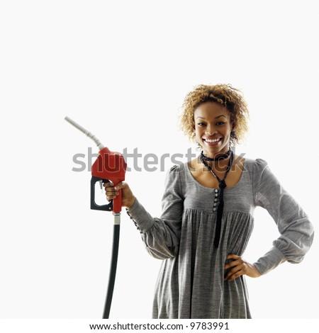 Woman holding gasoline pump nozzle smiling. - stock photo