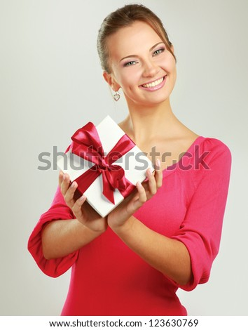 Woman holding gift box isolated on white background - stock photo