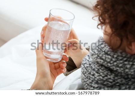 Woman holding glass with water with soluble tablet - stock photo
