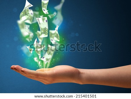Woman holding glowing paper moneys in her hand - stock photo