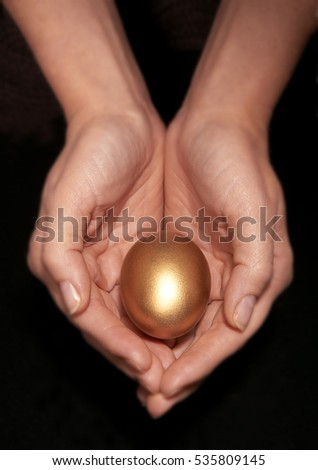 WOMAN HOLDING GOLD EGG IN CUPPED HANDS