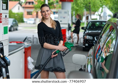 woman holding green nozzle at gas station - stock photo