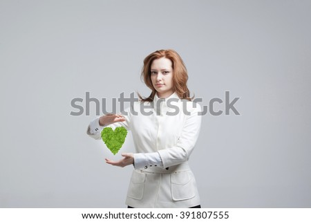 Woman holding green plant heart in her hands