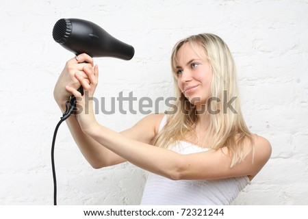 Woman holding hairdryer (focus on the hair dryer)