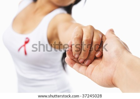 Woman holding hand to give support for AIDS cause or breast cancer,with red ribbon on her chest. PS:you can change the ribbon color to pink for breast cancer support cause as both using same symbol - stock photo