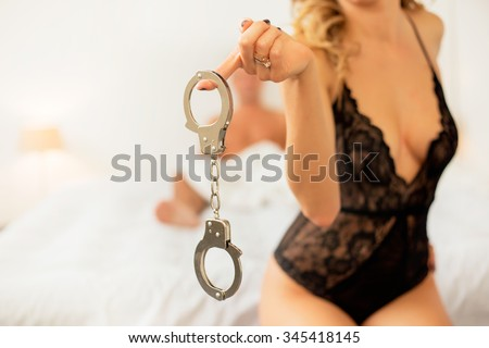Woman holding handcuffs  - stock photo