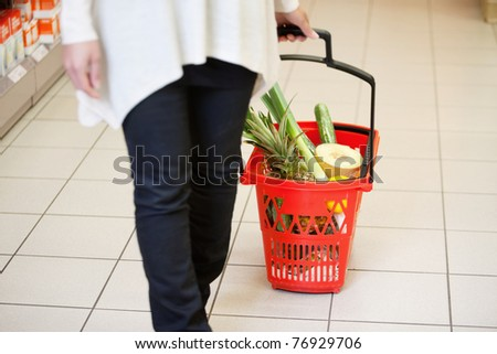 Woman holding handle of red basket in shopping store - stock photo