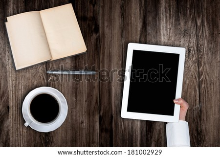 Woman holding hands of a tablet with blank screen on a wooden table coffee book's pen