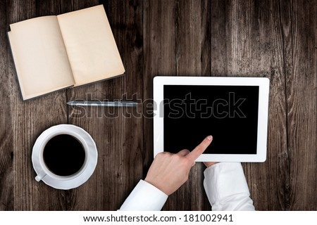 Woman holding hands of a tablet with blank screen on a wooden table coffee book's pen - stock photo