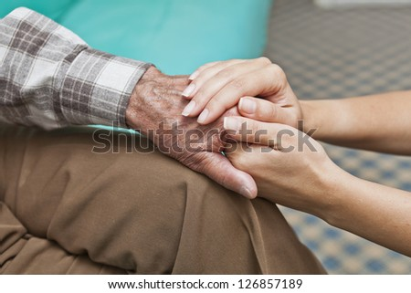 woman holding hands of grandfather - stock photo